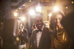 Smiling celebrity couple being photographed by paparazzi at event - stock photo