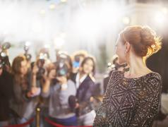 Celebrity turning and smiling at paparazzi photographers at event - stock photo