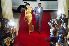 Celebrity couple arriving at red carpet event and being photographed by - stock photo