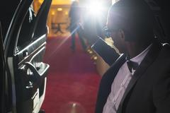 Celebrity in limousine arriving at red carpet event and waving to photographing Stock Photos