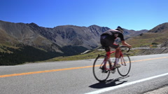 Road bike cyclist rides by camera in mountains - stock footage