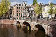 Bridge over Canal and Houses in Amsterdam Stock Photos
