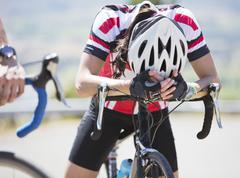 Disappointed cyclist resting on handlebars - stock photo