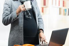 pregnant woman wearing casual clothes at work - stock photo