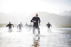 Triathletes emerging from water Stock Photos