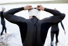 Triathlete adjusting goggles at start of race Stock Photos