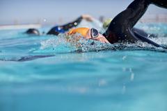 Triathletes in wetsuit splashing in pool Stock Photos