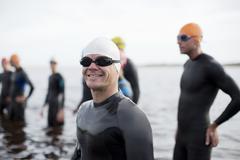 Triathlete smiling on beach - stock photo