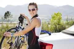 Woman attaching bicycle to car Stock Photos
