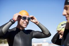 Triathlete adjusting goggles outdoors Stock Photos