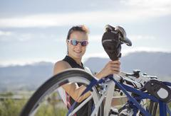 Woman taking bicycle off cycle rack Stock Photos