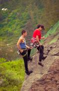 man and woman rapelling down mountain - stock photo