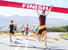 Runner crossing race finish line - stock photo