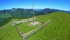 Flying over beautiful mountain landscape with wooden haymow at green meadow Stock Footage