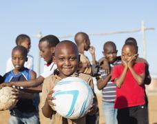 Boys holding soccer balls in dirt field Stock Photos