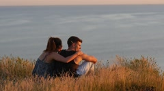 Stock Video Footage of Couple tenderly hugging each other sitting over a precipice in golden sunset