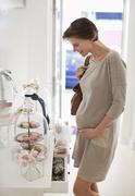 Pregnant woman admiring cookies in store - stock photo