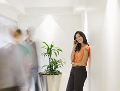 Businesswoman talking on cell phone in busy office hallway - stock photo