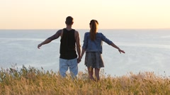 Couple young people lift up hands to the sky freedom over a precipice in sunset Stock Footage