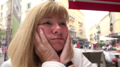 Stressed senior woman with headache sits in cafe Stock Footage