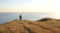 Stock Video Footage of Freedom concept and young couple hugging over a precipice in golden sunset