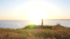 Girl photographer shoot on beautiful nature over a precipice in golden sunset Stock Footage