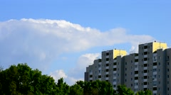 Beautiful cumulus clouds move behind modern apartment block Stock Footage