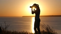Silhouete girl photographer shooting open air against golden sunset Stock Footage