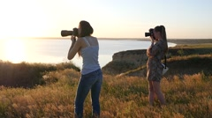 Two girls photographer shooting on nature over a precipice in golden sunset Stock Footage