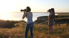 Stock Video Footage of Two girls photographer shooting on nature over a precipice in golden sunset