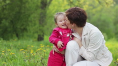 Mother and her daughter lying in grass and playing in summer garden Stock Footage