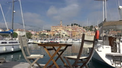 Table and chairs at Old town of Menton from across harbour, France Stock Footage