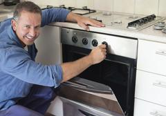 Electrician working on oven in kitchen Stock Photos