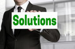 Solutions sign is held by businessman Stock Photos