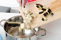Adding eggplant pieces into saucepan - stock photo