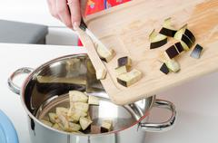 Adding eggplant pieces into saucepan Stock Photos