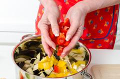 Adding red pepper pieces into saucepan - stock photo