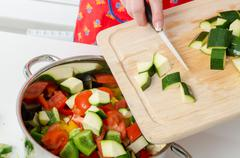 Adding zucchini pieces into saucepan - stock photo