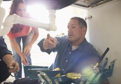 Plumbers working on pipes under sink Stock Photos