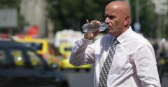 Stock Video Footage of Torrid Hot Day Thirsted Businessman Wait Associate Sweating Outside Drink Water