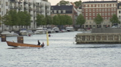 Pan of dinghy boat in Copenhagen harbour Stock Footage