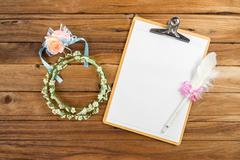 Clipboard attach planning paper with pen beside rose headband - stock photo