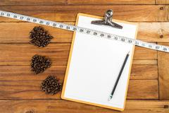 Wooden Clipboard attach planning paper with pencil on top beside coffee bean, - stock photo