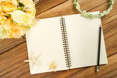 Planning paper with pen, rose headband, tiara, bouquet, starfish - stock photo