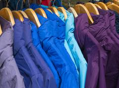 Rainproof jackets in bright colors on a rack for sale. - stock photo