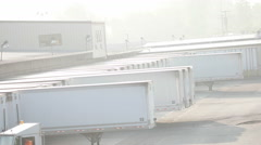 White semi trailers lined up at a dock as truck passes in front Stock Footage