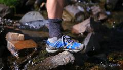 Hiker stepping crossing a stream Stock Footage