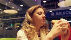 Pretty girl eats burger Stock Footage