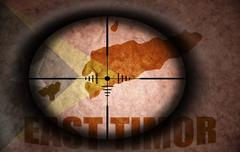 Sniper scope aimed at the vintage east timor flag and map Stock Illustration