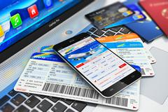 Buying air tickets online via smartphone - stock photo